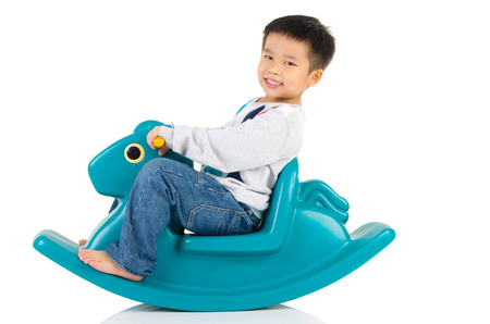 singaporean: smiling asian boy playing with Toy horse