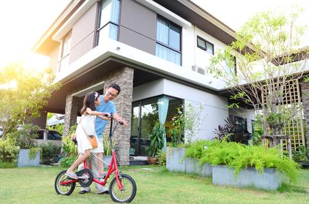 Gezonde vader en dochter spelen samen buiten hun nieuwe huis. Home leuke levensstijl, familie concept.