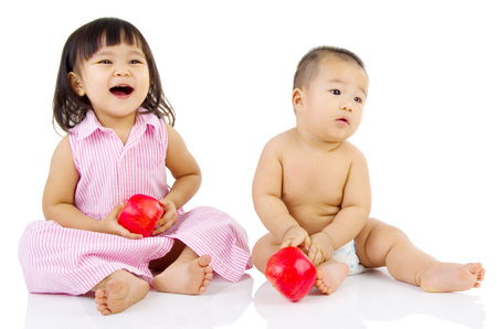 niños sanos: Portrait of lovely asian kids holding an apple playing on the floor