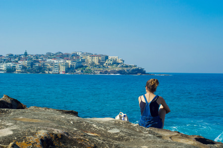 resort life: young woman against the blue sea