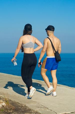 Couple exercise along the beach Stock Photo