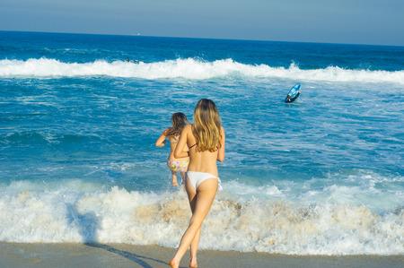Zwei schöne junge Mädchen laufen im Meer Standard-Bild - 84876840