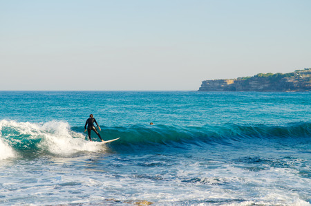 Surfers catching the waves in the waters of Bondi Beach in Sydney Australia.