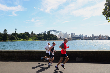 SYDNEY - AUGUST 11 2017:Australian men runs near the Opera House. Approximately 35% of the Australian population participated at least in one physical recreation activity. 新聞圖片