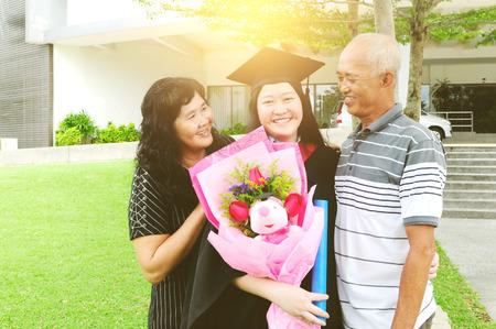Asian university student and family celebrating graduation outdoor