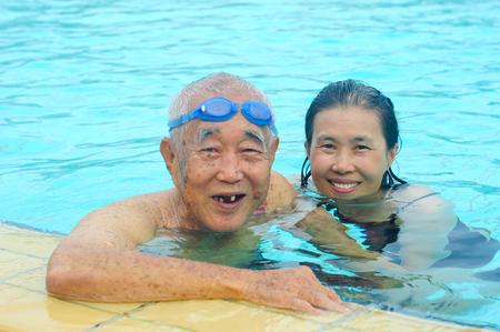 아시아 아버지와 딸이 수영장에서 카메라를 찾고