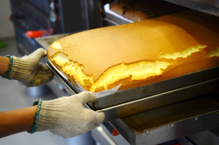 Baker taking out taiwanese traditional sponge cake from the oven Stock Photo