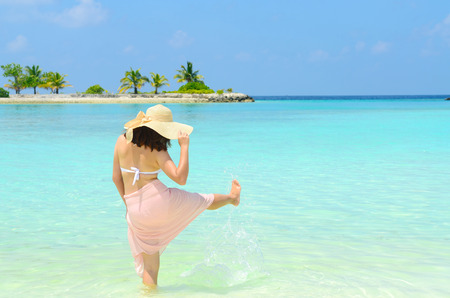 Beautiful asian young woman in sunhat relaxed and playing water at tropical beach in Maldives