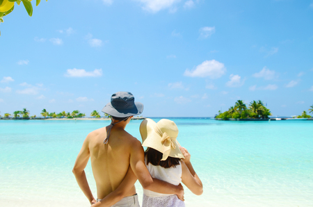 Young happy asian couple  in sunhat on white beach at summer vacation in Maldives island