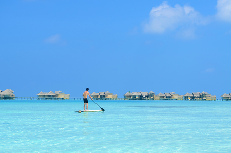 Young asian man paddle board rowing on sunny tropical paradise island with blue  sea water ocean in Maldives island. Standard-Bild
