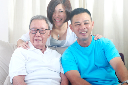 Asian senior father with his adult son and daughter at home. Family living lifestyle. 免版税图像
