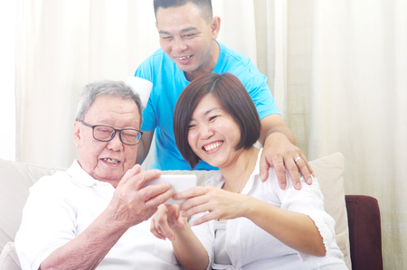 Tecnologia moderna, concetto di età e persone. Uomo anziano asiatico con sua figlia e suo figlio che si fanno selfie, usano lo smartphone, si fotografano Archivio Fotografico