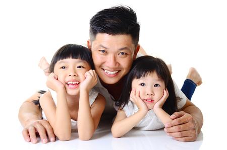 Padre asiático y sus lindas hijas aislado sobre fondo blanco. Foto de archivo