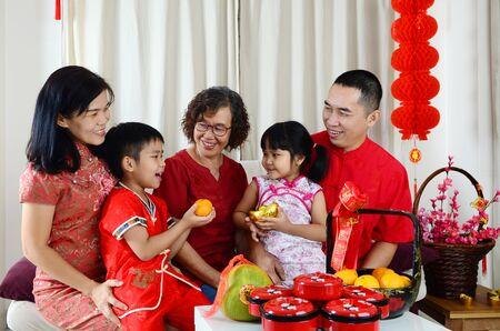 Asiatische Familie feiert chinesisches Neujahr. Chinesische Schriftzeichen auf dem Foto bedeuten