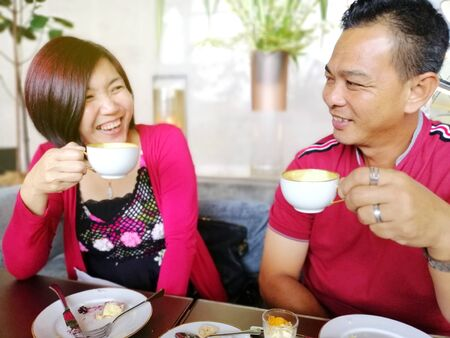 An Asian middle age lovely couple date  in a cafeteria, spending time together.