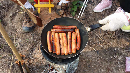 fry sausages on a fire in a pan at forest during summer time.