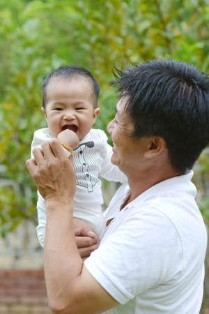 Happy father's day! joyful young dad hugging his cute son at outdoor park. Archivio Fotografico