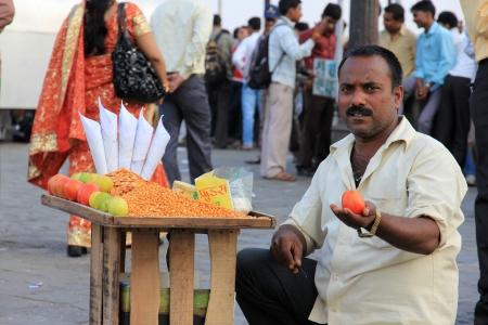 Mumbai, India - October 26, 2011 Unidentified Indian man sells roasted nuts, tomato and lemon at the Gateway of India