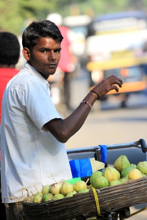 pune: Pune, India - October 22, 2011 Unidentified Indian man sells guava beside street in Pune city