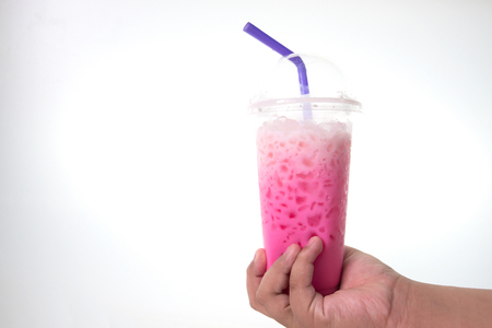A beautifully colored drink in a glass on the hand of someone holding a white backdrop.