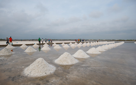 People are working together on the traditional salt making process of Asian people in Thailand. Stock Photo