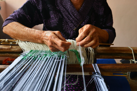 Blurry images. The hand of an elderly woman who is picking up the yarn is a gesture of traditional Asian weaving. Stock Photo