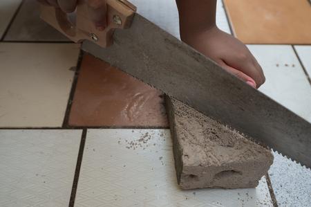 Close up of a man cutting sawn at a concrete slab resting on a ceramic tile background. Reklamní fotografie