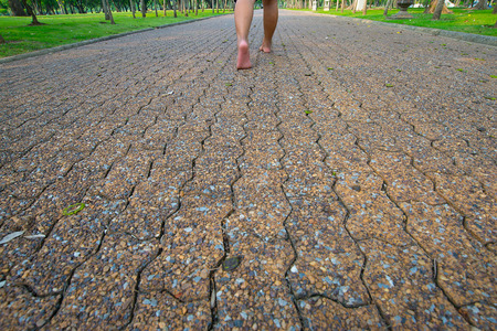 The man was walking on the road barefoot in the park.