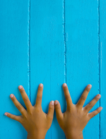 The fingers spread on the blue background.