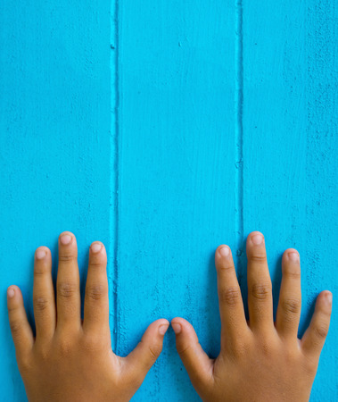The finger and nail of a young child on a blue wooden floor.