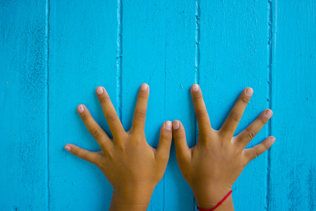 The hands that spread their fingers were laid on a wooden floor painted blue.
