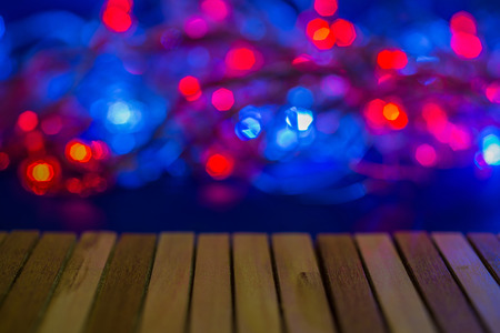 top Empty wood table with sparkling backdrop, burgundy light, flashy colors and blurry. Stock Photo