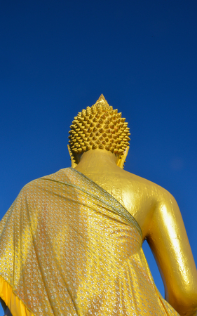 Behind the Buddha is located in the forest with blue sky background in the morning. Stock Photo