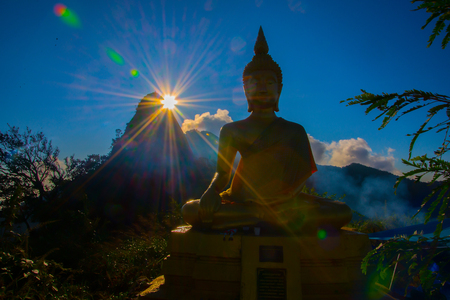 The Buddha is located in the jungle with shining sunlight in the morning. Stock Photo