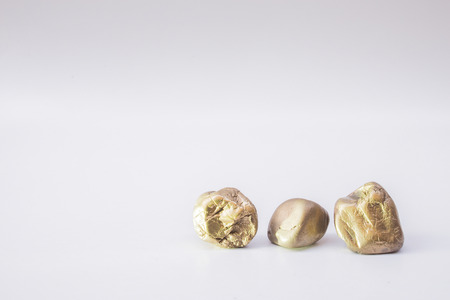 Balance the concept of placing different gold stones together on a white background with space.