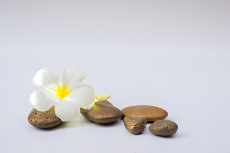 Relaxed concept, white stones stacked with balance and refreshing white flowers on a white background.
