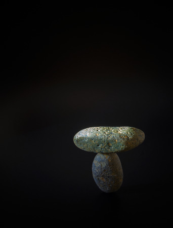 Balance concept, natural texture stones are nestled together in balance on a black background. Stock Photo