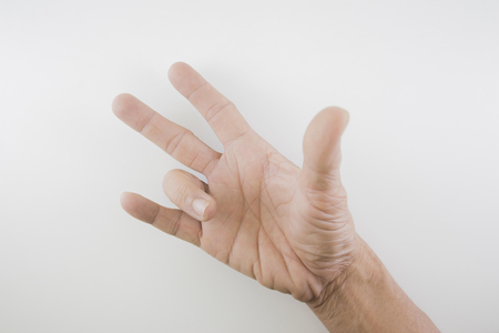 Finger of seniors who have problems trigger fingers on a white background. 版權商用圖片 - 104092904