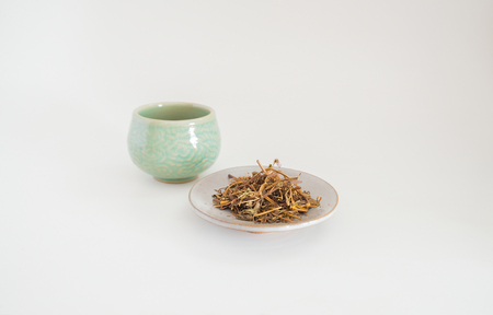 Dried tea with a cup of tea on a white background.