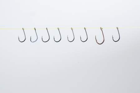Hooked hooks with yellow ropes hang many together on a white background with empty space.