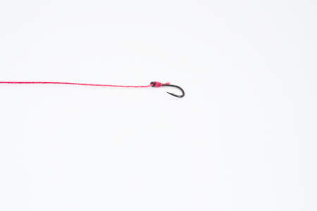 A hook hooked with red ropes on a white background with empty space.