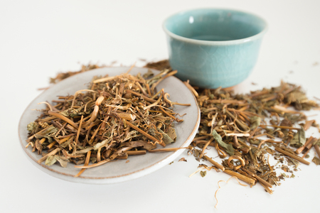 Dried tea leaves with a cup of tea on a white background.