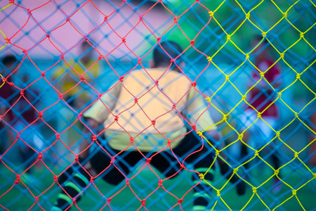 The net of the football goal and the blurred image of the footballer playing in the game. Stock Photo
