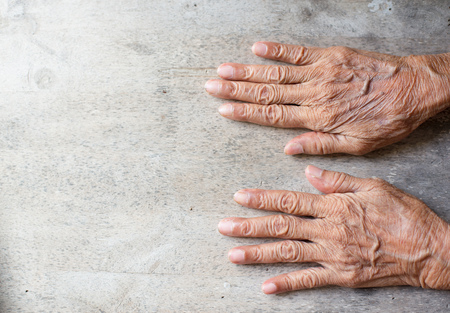 The hand of the old man with dried wrinkles, laying hands on old wooden floor. Stock Photo