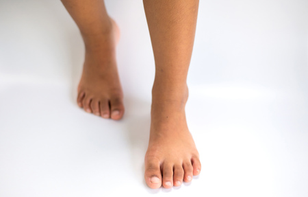 Feet Both bare feet pedal on a white background.