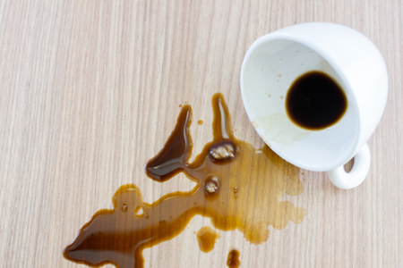The coffee spill falls and the coffee splits on the wooden floor.