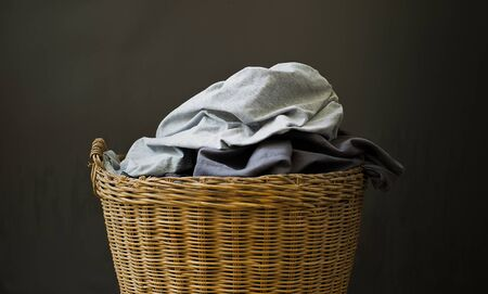 Used clothes in the basket are placed on a gray background.