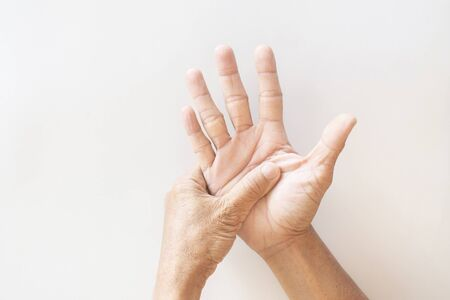 The hands and fingers of the elderly with signs showing illness on a white background