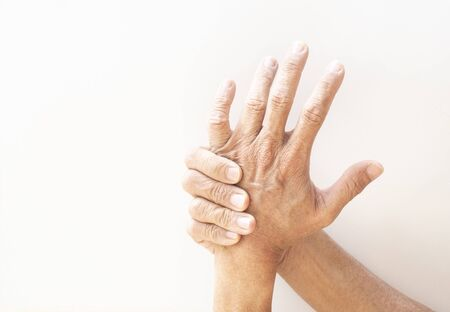 The hands and fingers of problem seniors showing signs of illness on a white background.
