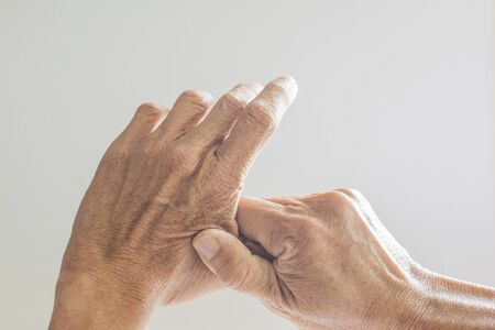 The hands and fingers of elderly people showing signs of illness on a white background